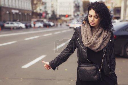 Brunette beautiful caucasian woman in scarf on a european city s