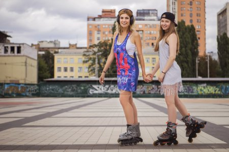 Two young beautiful blonde hipster girls on summer day having fu