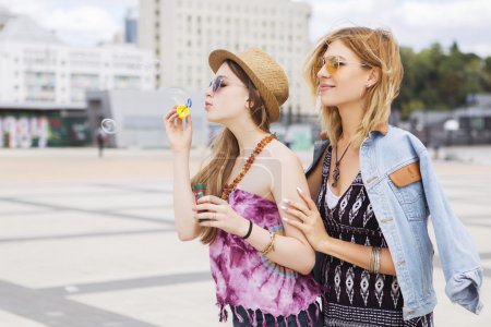 Photo for Two young beautiful blonde hipster girls on summer day having fun in european city blowing bubbles. Copy space - Royalty Free Image