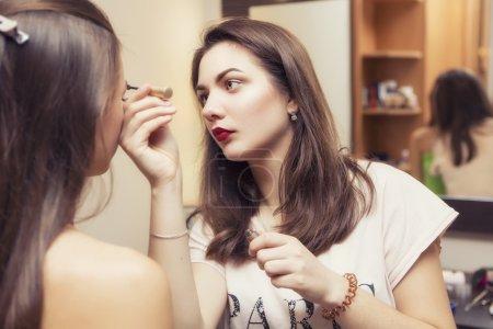 Brunette make up artist woman applying make up for a brunette br