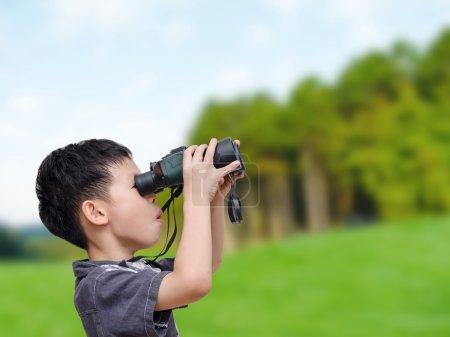 Boy using binoculars in forest