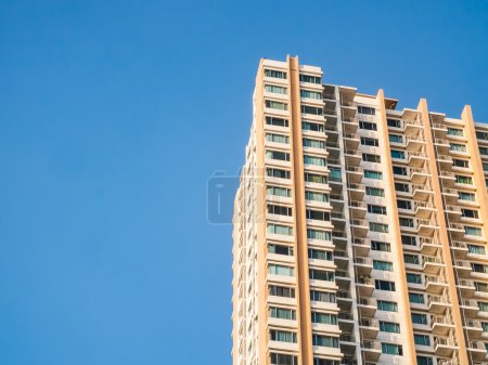 Apartment building and blue sky background.