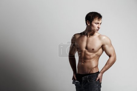 Handsome athletic man looking at side in unbuttoned jeans. Stron