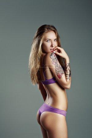 pretty girl with much tattoo in purple lingerie biting finger bi