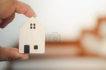 Photo pour Mains masculines tenant une petite maison de jouets. Concept de maison à vendre. - image libre de droit