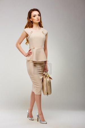 Photo pour Jolie fille dans des vêtements à la mode élégantes, marcher sur une graybackground. Beauté, mode, style. - image libre de droit