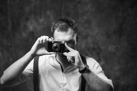 Photo pour Bel homme en chemise posant sur un fond de mur gris - image libre de droit