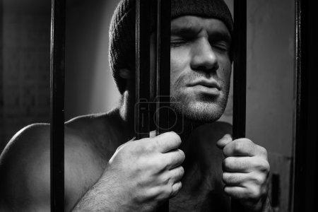 Foto de El preso se preocupa de una conducta criminal está detrás de un enrejado - Imagen libre de derechos