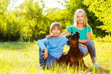 blonde girl and boy hugs beloved dog or doberman in summer park
