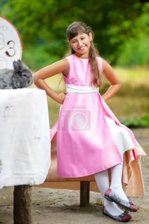 Photo for Girl sits at table and looks at the rabbit. Alice in Wonderland concept - Royalty Free Image