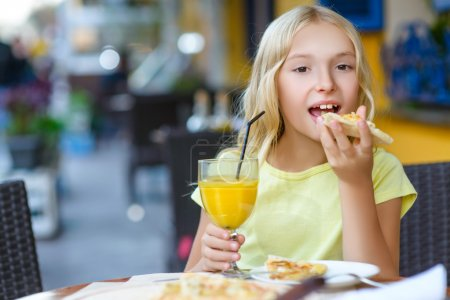 Photo for Pretty girls smiling when drinking juice and eating pizza - Royalty Free Image