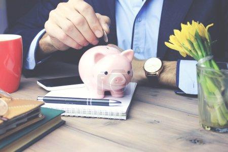 Photo pour Homme, mettre de l'argent dans la tirelire sur table - image libre de droit