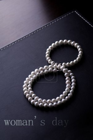 Photo for Pearl necklace in the shape of eights on a black leather - Royalty Free Image