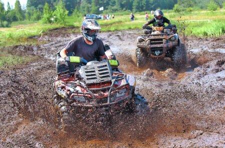 Photo pour Un VTT pulvérise la boue comme il zips autour d'un coin à un rallye dirt road - image libre de droit