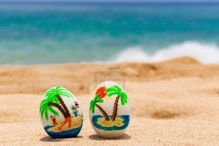 Photo pour Oeufs de Pâques, ornée de palmiers sur la plage de l'océan - image libre de droit