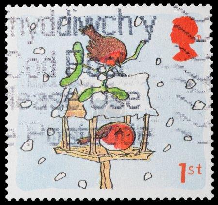 Photo pour Royaume-Uni - circa 2001 : un timbre du Royaume-Uni montre illustration de deux robins à une neige couverts mangeoire à oiseaux, vers 2001 - image libre de droit