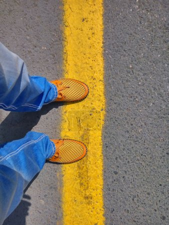 Man in jeans and a yellow shoes standing on the yellow band