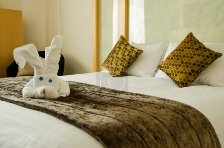 Photo pour Chambre blanche marron avec peluche blanche sur la housse de lit marron . - image libre de droit