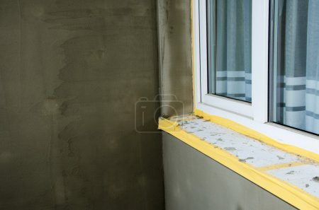 Photo for Semifinished repairing of balcony, gray plaster and dirty white window. - Royalty Free Image