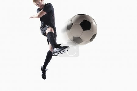 Athlete kicking soccer ball