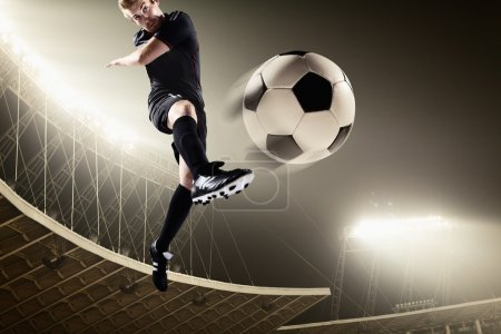 Athlete kicking soccer ball in stadium