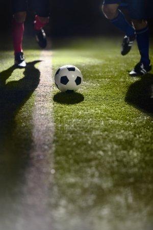 soccer players running towards a soccer ball