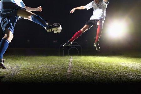 Deux joueurs de football taper dans un ballon de football
