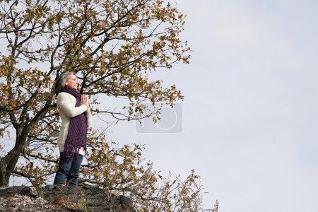 Femme priant sur un rocher