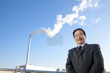 Businessman in Front of Smokestack