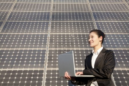 Businesswoman on Laptop in front of Solar Panel