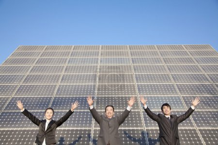 Businesspeople with Arms Outstretched in front of Solar Panel