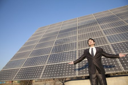 Businessman with arms outstretched in front of solar panels