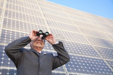Businessman looking through binoculars in front of solar panels