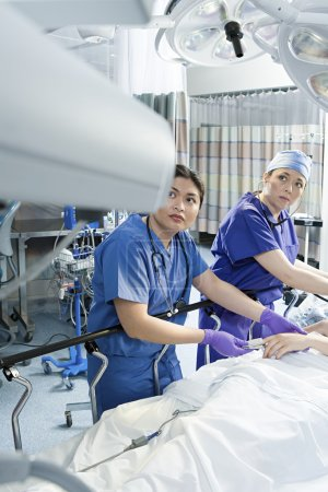 Surgeons with patient in operating theatre