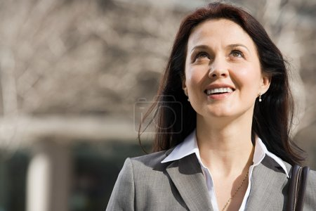 Businesswoman looking up and smiling