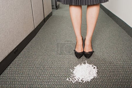 Businesswoman stood in front of pile of paper shreddings