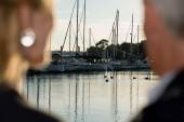 Couple looks to yachts in harbour
