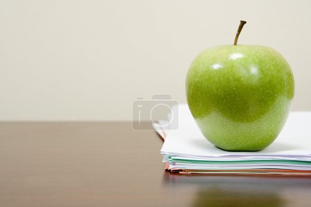 Apple on a pile of papers