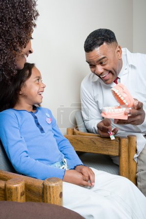Dentist showing patient how to clean teeth