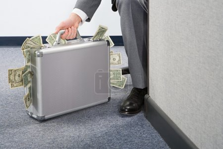 Businessman holding briefcase with money