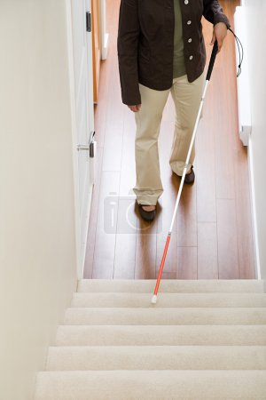 Blind woman using a walking stick on stairway