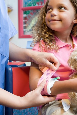 Nurse putting bandage on girl