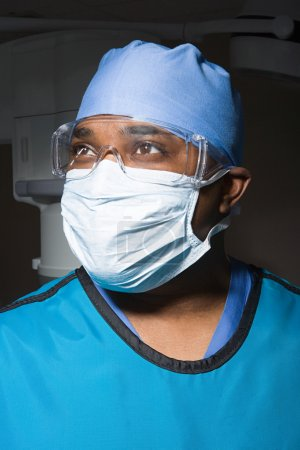 Surgeon in mask and safety goggles