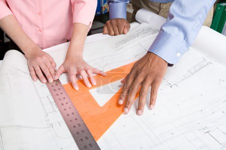 Architects measuring blueprint