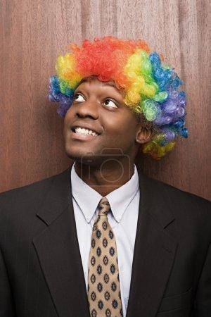 Businessman wearing clowns wig