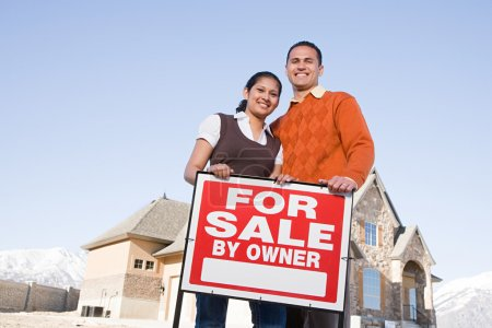 couple hold a for sale sign