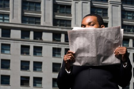 Businessman looking over newspaper