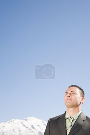 Businessman thinking by mountains