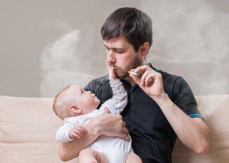 Photo pour Mauvais père est fumeur et tenant le petit bébé dans mains. - image libre de droit