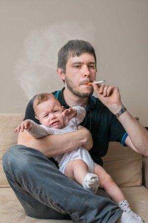 Photo pour Mauvais père est cigarette fumer et tenue bébé. - image libre de droit
